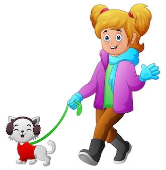 Menina com roupas de inverno caminhando com seu gato