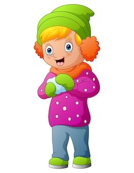 Menina com roupas de inverno jogando uma bola de neve