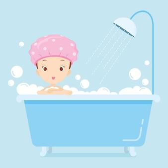 Menina com touca de banho tomando banho na banheira com espuma de sabão