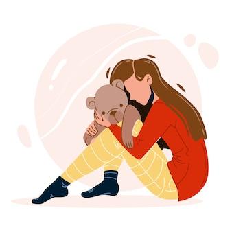 Menina com trauma abraçando o brinquedo do urso de pelúcia