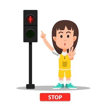 Menina com um gesto de pare quando o indicador luminoso da faixa de pedestres fica vermelho