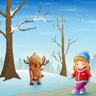 Menina com veados no campo de neve
