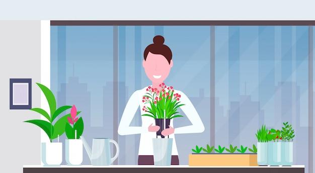 Menina cute housewife transplante planta em novo potenciômetro mulher feliz cuidar retrato moderno apartamento casa jardinagem interior conceito horizontal