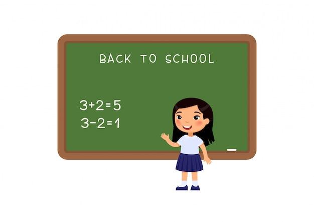 Menina da escola que está no quadro-negro liso.