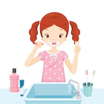 Menina de pijama escovando os dentes no banheiro