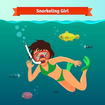 Menina de snorkel no mar com peixes