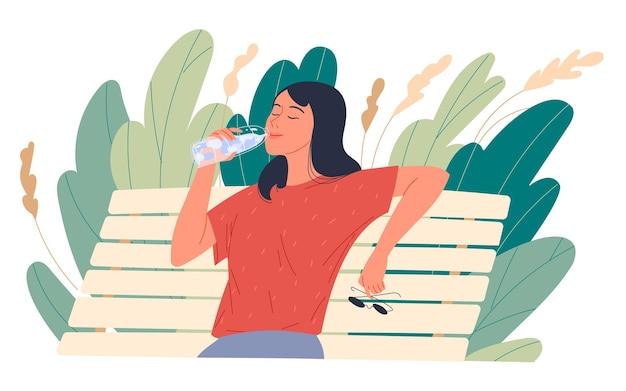 Menina, desfrutando de água potável, enquanto está sentado em um banco do parque.