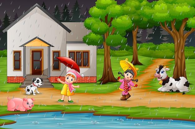 Menina dos desenhos animados dois brincando com animais sob a chuva