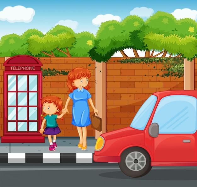Menina e mãe em pé na calçada