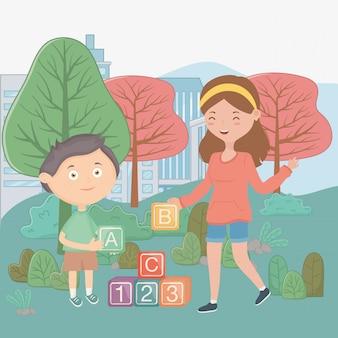 Menina e menino com blocos de alfabeto no parque da cidade, brinquedos para crianças