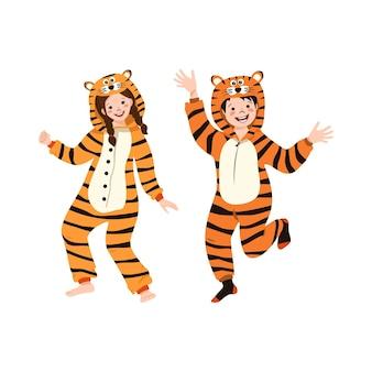 Menina e menino com fantasia de carnaval laranja de tigre. festa do pijama de crianças. crianças em macacões ou kigurumi, roupas festivas para o ano novo, natal ou feriado