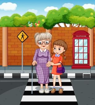Menina, e, senhora velha, cruzando estrada