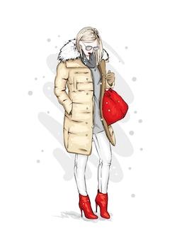 Menina elegante com um casaco de inverno da moda, botas e uma bolsa.