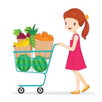 Menina empurrando o carrinho de compras com muitas frutas, alimentação saudável