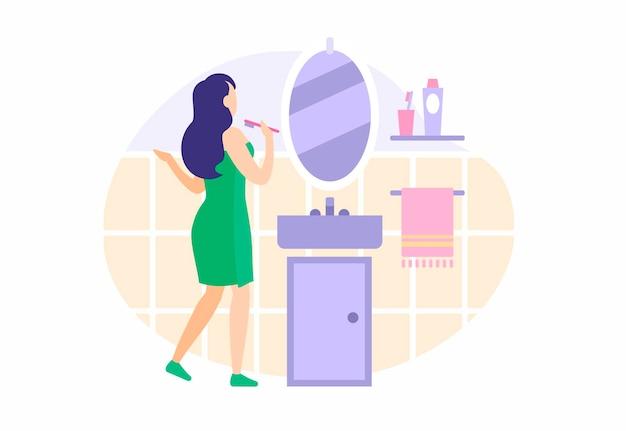 Menina escova os dentes no banheiro. linda mulher amarrada com toalha verde lava o rosto olhando no espelho. rotina de higiene matinal para uma limpeza saudável. ilustração em vetor plana