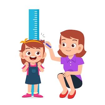 Menina feliz criança fofa, medindo a altura com a mãe