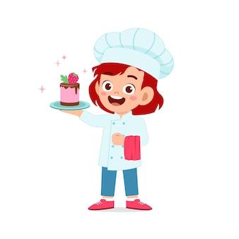 Menina feliz e fofa usando uniforme de chef e cozinhando um bolo de aniversário