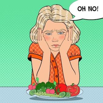 Menina infeliz com prato de legumes frescos