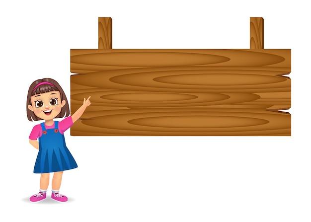 Menina mostrando o dedo indicador para uma placa de madeira em branco