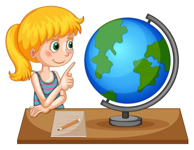 Menina olhando o globo em cima da mesa