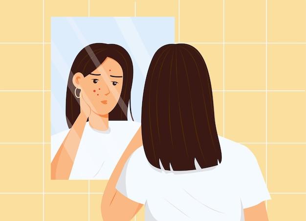 Menina olhando para o rosto com acne no espelho do banheiro