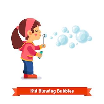 Menina pequena que sopra bolhas de sabão através da varinha