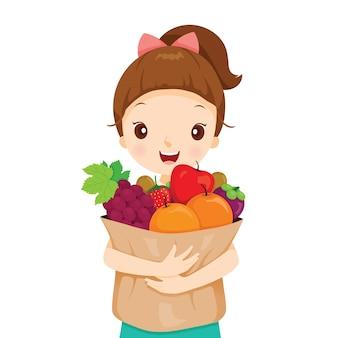 Menina segurando uma sacola cheia de frutas, alimentação saudável