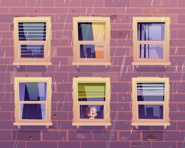 Menina triste olha pela janela para a chuva, fora da fachada do prédio com parede de tijolos