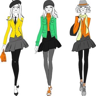 Meninas bonitos bonitos da moda hipster em jaquetas, saias e bonés com bolsas.