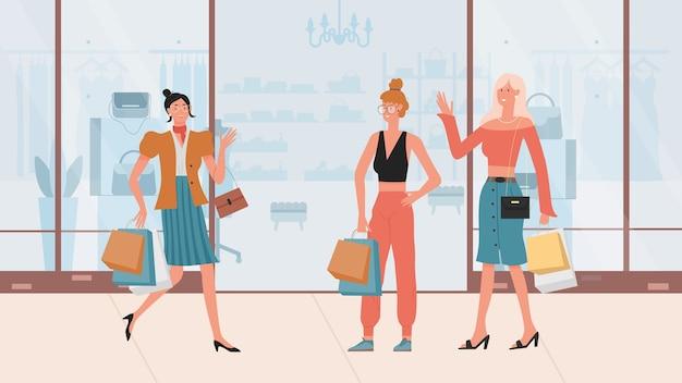 Meninas da moda caminhando após as compras segurando uma bolsa