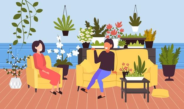 Meninas discutindo durante reunião mulheres relaxantes na moderna sala de estar com plantas de casa verde interior