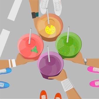 Meninas esportivas pegando smoothies nas mãos