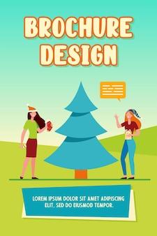 Meninas felizes decorando modelo de folheto de árvore de natal