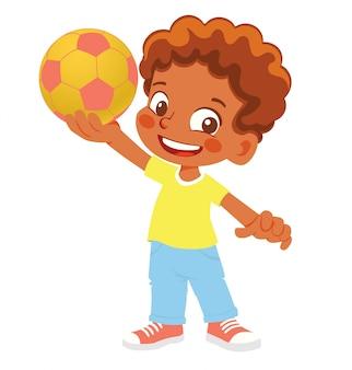 Menino afro-americano detém uma bola de futebol. menino em pé com a bola