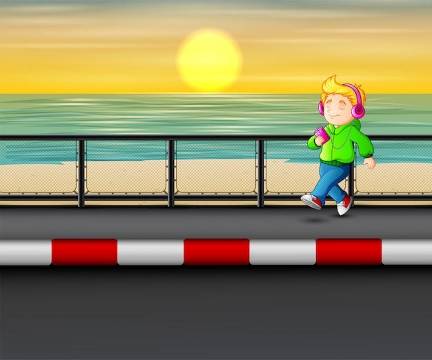 Menino andando ouvindo música player à beira-mar