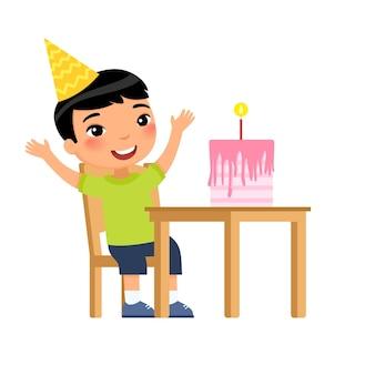 Menino asiático com bolo de aniversário e vela na mesa