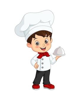 Menino bonitinho chef segurando uma bandeja de prata