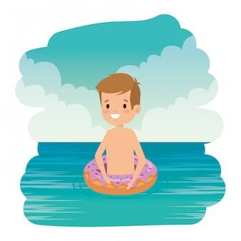 Menino bonitinho com roupa de banho e donut flutuar no mar