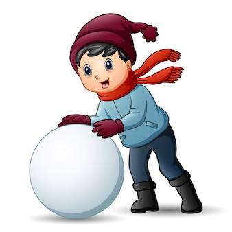Menino bonitinho com roupas de inverno jogando uma bola de neve