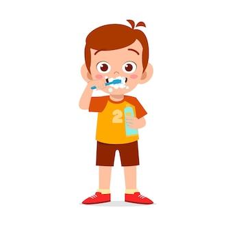 Menino bonitinho escovando os dentes e segurando pasta de dente