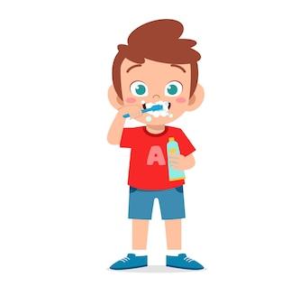 Menino bonitinho escovando os dentes e segurando uma ilustração de pasta de dente