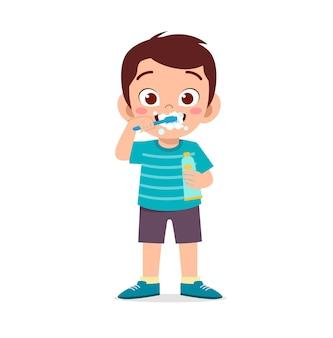 Menino bonitinho escovando os dentes e segurando uma pasta de dente