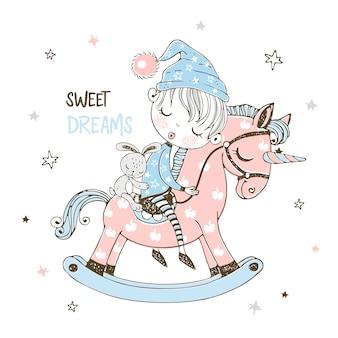 Menino bonitinho está dormindo docemente em um cavalo de brinquedo de unicórnio.