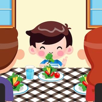Menino bonito de desenho animado gosta de comer vegetais e os pais dela o apreciaram