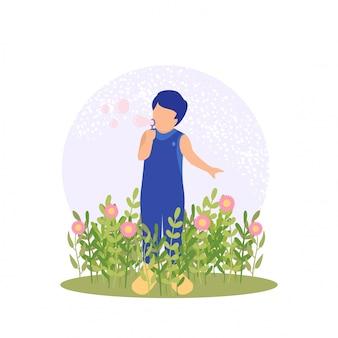 Menino bonito de primavera jogando flor e bolha no jardim