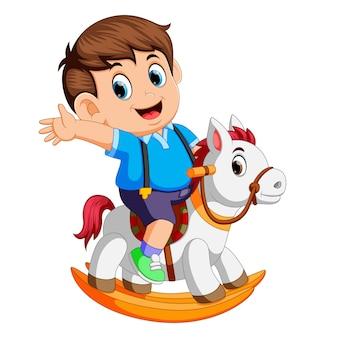 Menino bonito em um cavalo de brinquedo