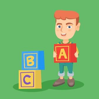 Menino caucasiano de sorriso que joga com cubos do alfabeto.
