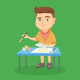 Menino caucasiano, desenhando uma foto com um pincel