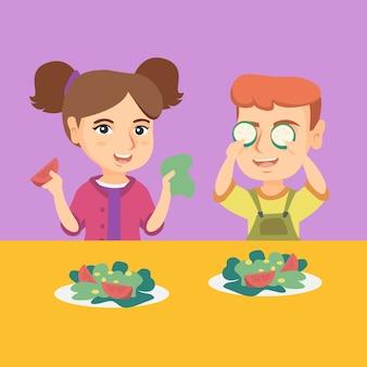 Menino caucasiano e menina que jogam com vegetais.