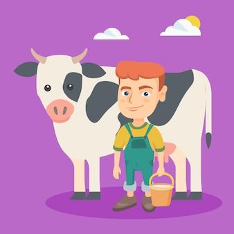 Menino caucasiano pequeno do fazendeiro que ordenha uma vaca.